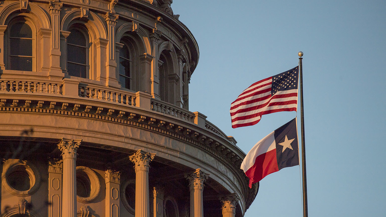 The U.S. and Texas flags flying at the Texas Capitol in Austin