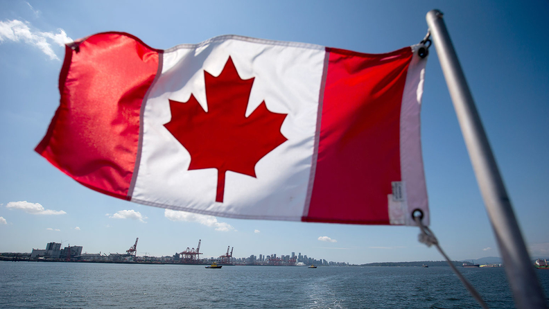 Canadian flag with shoreline in the background