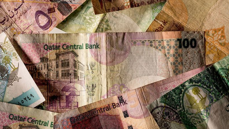 A Qatari 100 riyal banknote with other denominations of banknotes issued by the Qatar Central Bank