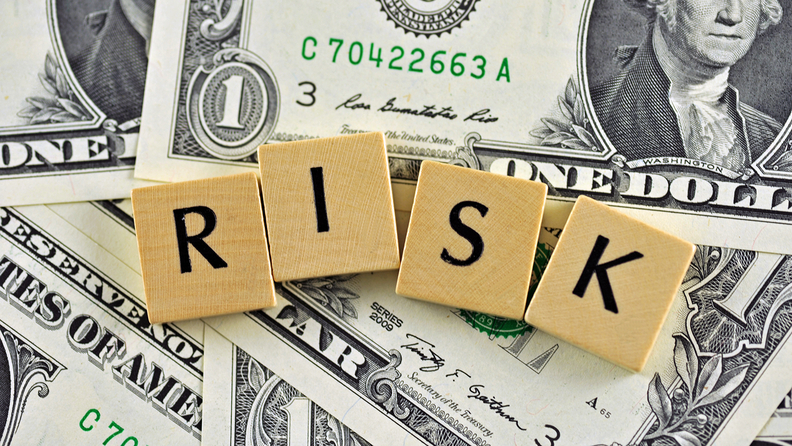 Wooden blocks that spell RISK on a background of $1 bills