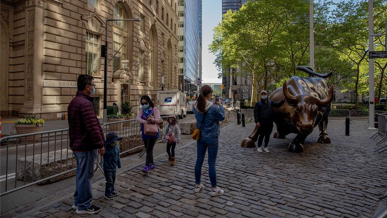 People take photographs in front of the Charging Bull bronze statue in the Financial District of New York as the city's finance industry, slowly, is getting back into the office
