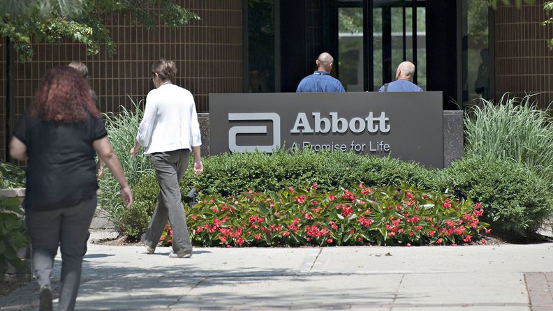 Employees walk near an Abbott Laboratories sign at the company's headquarters complex in Abbott Park, Ill.