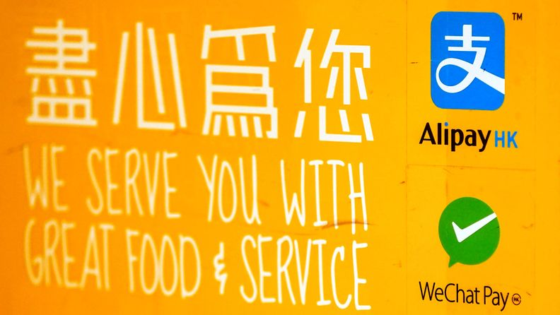 Signage for Ant Group Co.'s Alipay digital payment service, top right, and Tencent Holdings Ltd.'s WeChat Pay at a restaurant in Hong Kong