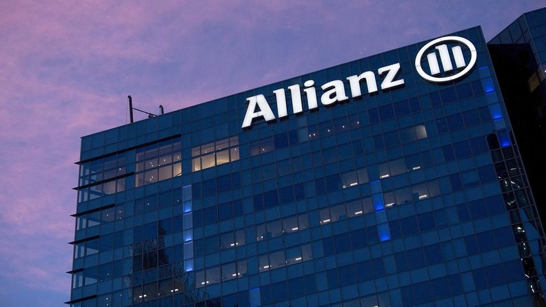 A lighted Allianz logo on the side of an office building at dusk