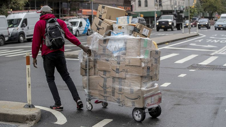 A worker wheels a cart of Amazon packages during a delivery in New York on Oct. 13, 2020