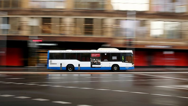 A bus travels along a road the central business district of Sydney