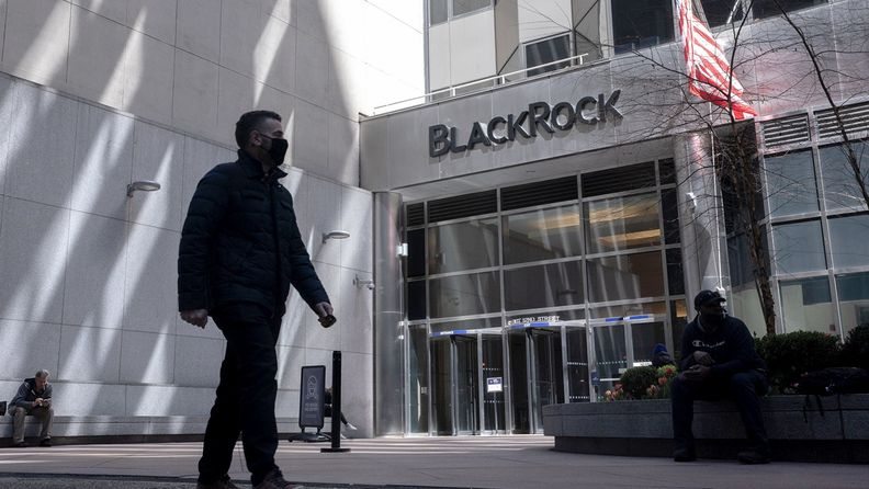 A pedestrian wearing a protective mask walks past BlackRock headquarters in New York
