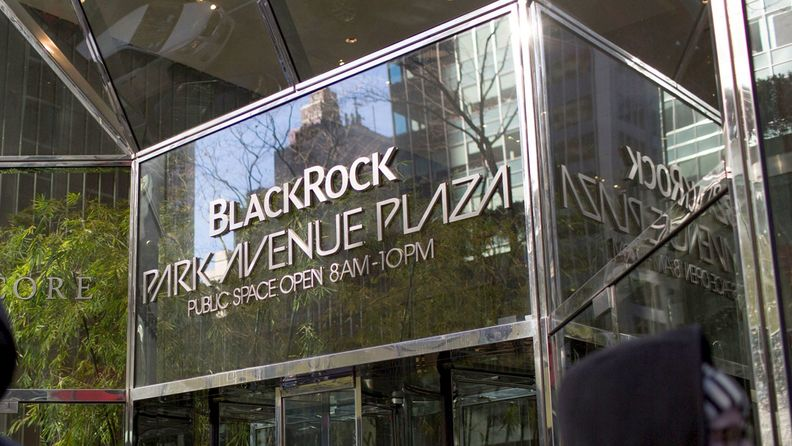 Pedestrians pass in front of BlackRock Inc. Park Avenue Plaza in New York