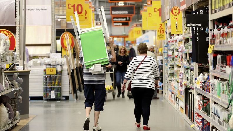 A customer carries garden chairs through an aisle inside a B&Q home improvement store, operated by Kingfisher