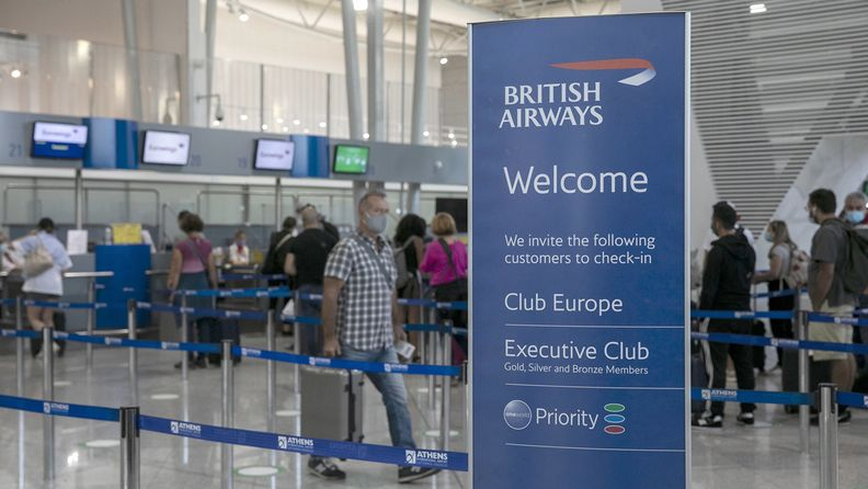A British Airways sign in front of travelers lining up at check-in counters at Athens International Airport in Greece on Sept. 17, 2020