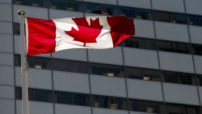 A Canadian flag flies outside a building in the financial district of Toronto