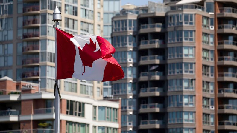 A Canadian flag flies over Granville Island Public Market in Vancouver, British Columbia