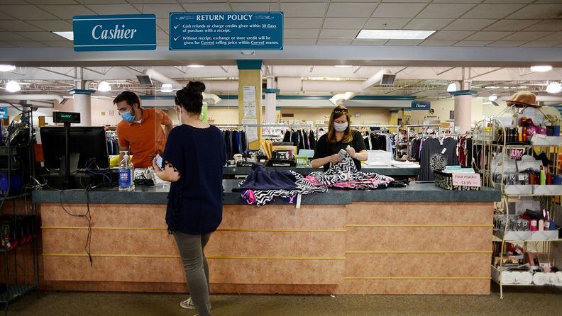 A cashier standing behind a protective barrier assists a customer at a Peter Harris Clothes store in Latham, N.Y.
