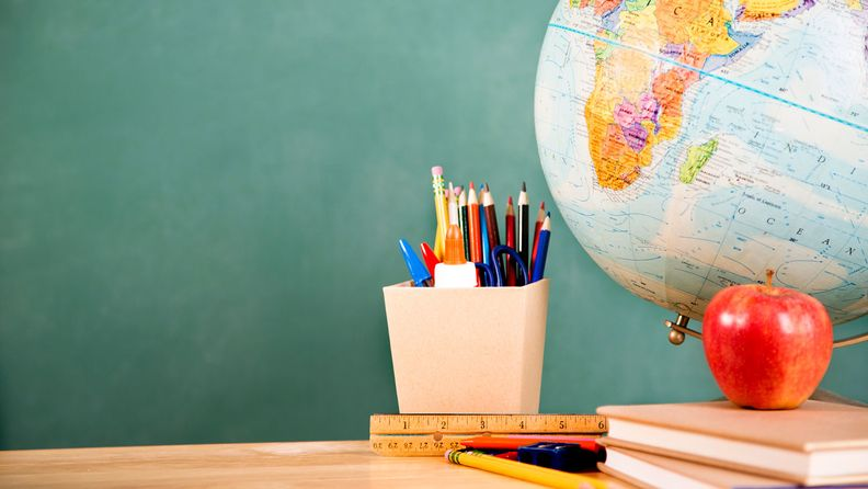 A globe with school supplies on top of school desk with chalkboard in background