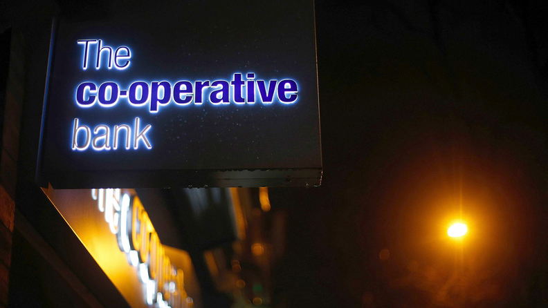 An illuminated logo sits on a sign outside a Co-Operative Bank Plc branch, a unit of Co-Operative Group Ltd., at night in Manchester, U.K.
