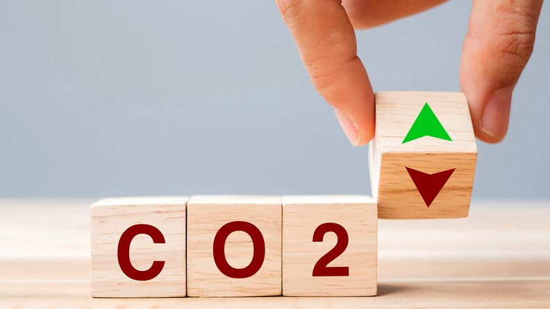 hand flipping wooden cube blocks to up and down arrow symbol with CO2 text on table background