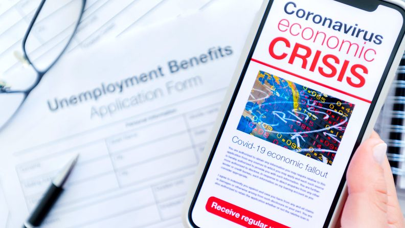 Close up of a mobile phone with coronavirus COVID-19 economic crisis news article, with an unemployment benefits claim form in the background on the desk.