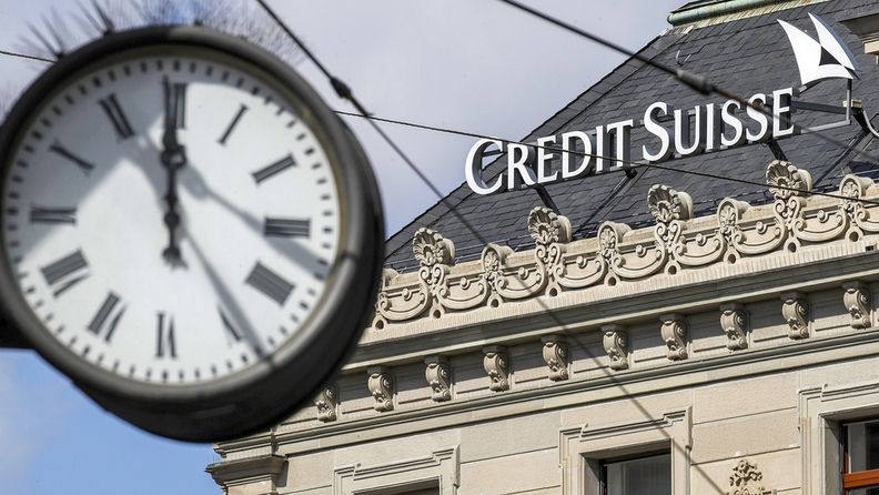 Credit Suisse log on the roof of a building with clock in the foreground