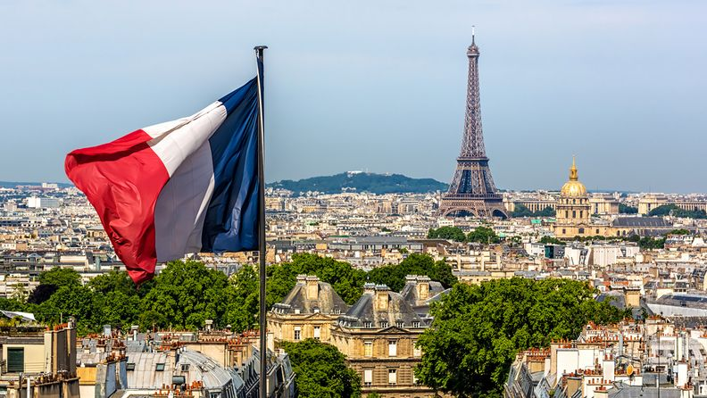 Paris skyline with French flag in foreground and Eiffel Tower in background