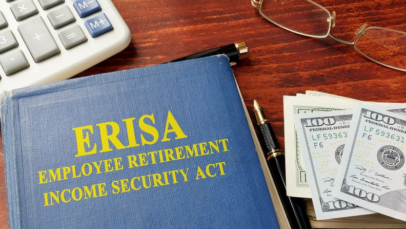 Book titled 'ERISA: Employee Retirement Income Security Act' with calculator, eyeglasses and $100 bills arranged on a desktop