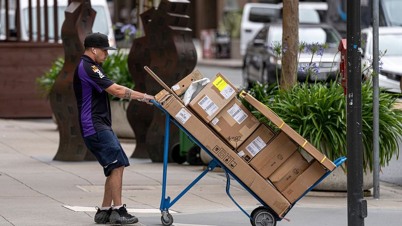 A driver for FedEx pulls a cart with packages in San Francisco,