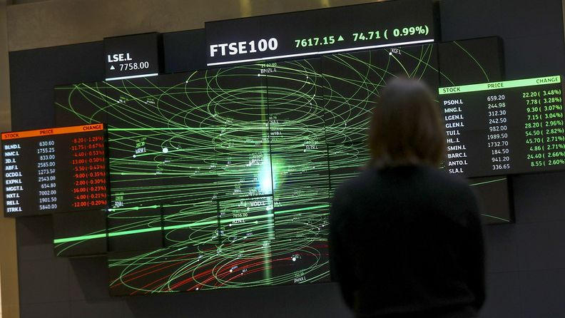 An employee views a FTSE share index board in the atrium of the London Stock Exchange Group's offices in London on Jan. 2, 2020