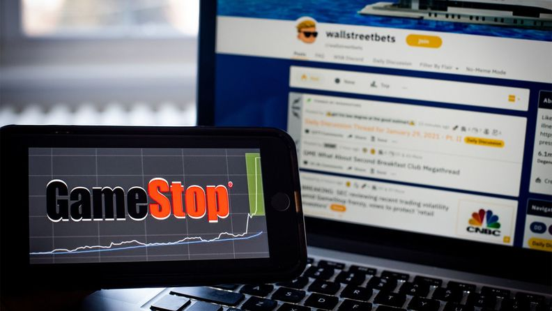 The WallStreetBets forum on the Reddit Inc. website on a laptop computer and the GameStop logo on a smartphone in an arranged photo.
