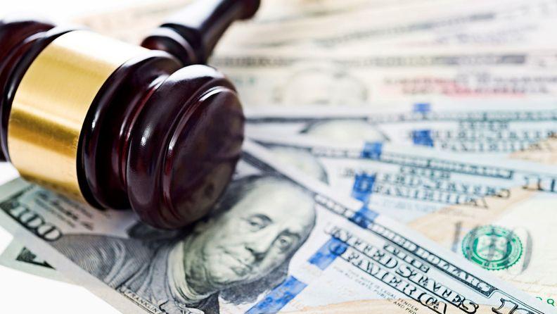 A gavel laying atop $100 bills
