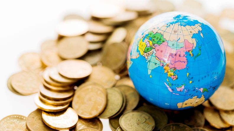 Close up of golden coins and globe