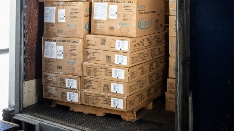 Boxes of Newell Brands Inc. Graco baby products sit stacked on a pallet inside a delivery truck