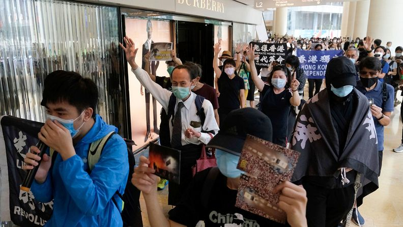 Demonstrators march past a Burberry Group Plc store inside Pacific Place shopping mall in the Admiralty district during a protest in Hong Kong.