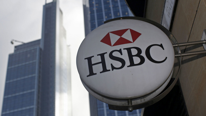 An HSBC logo sits on a sign outside the entrance to a bank branch, operated by HSBC Holdings Plc, in London, U.K.