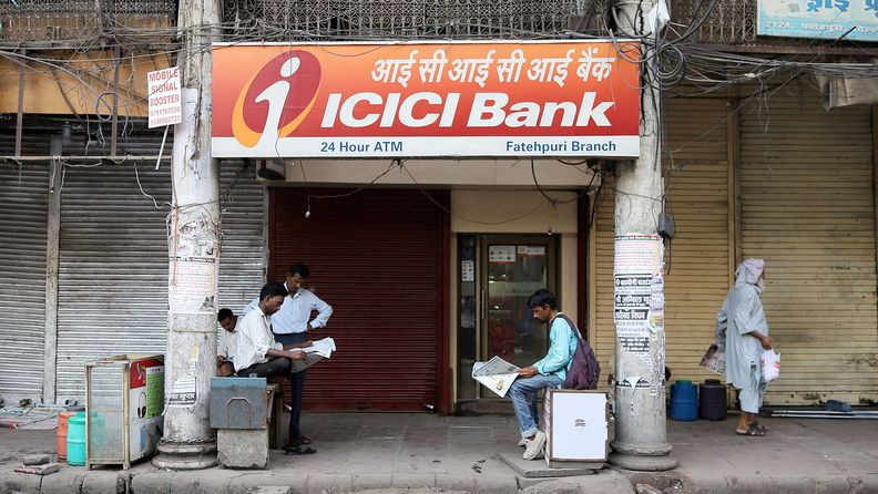 People sit reading newspapers outside an ICICI Bank Ltd. branch in Delhi