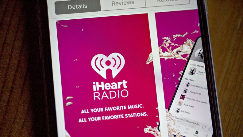 The iHeartMedia application is seen in the App Store on an Apple iPhone