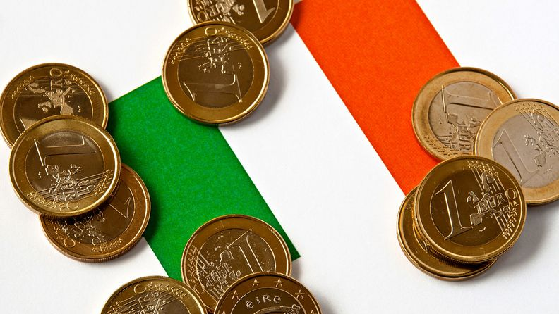 Close-up of an Irish flag and euro coins