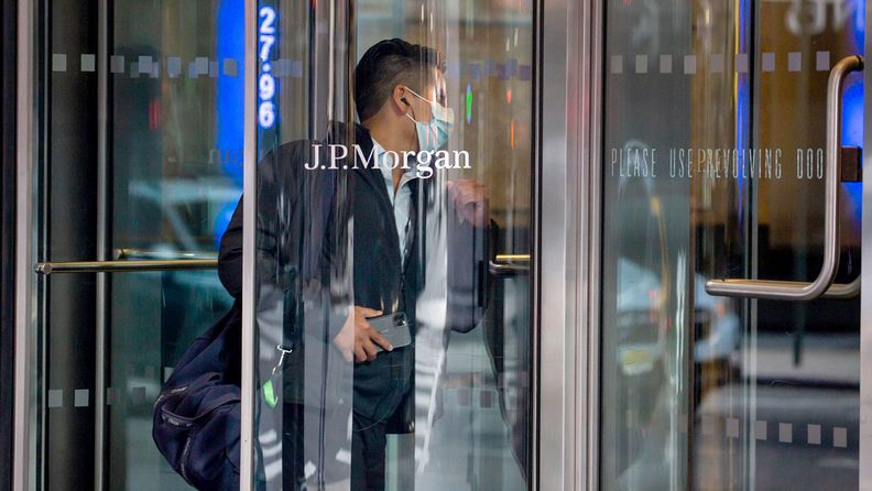 A person wearing a protective mask enters J.P. Morgan Chase & Co. headquarters in New York