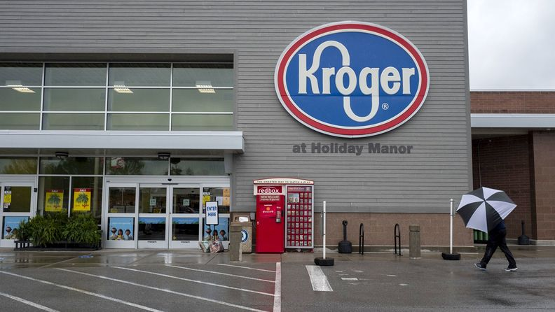 A shopper holding an umbrella walks towards a Kroger Co. grocery store in Louisville, Ky.