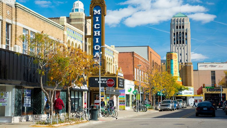 People walking in the sidewalk of Liberty Street in downtown Ann Arbor, with storefronts and the Michigan Theater sign, State Theater sign, cars and parked bicycles in the scene, and the Burton Memorial Tower in the distance, during a day with a blue sky with clouds