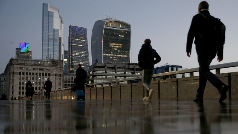 Commuters cross London Bridge in view of skyscrapers in the City of London square mile financial district in London on Dec. 14, 2020