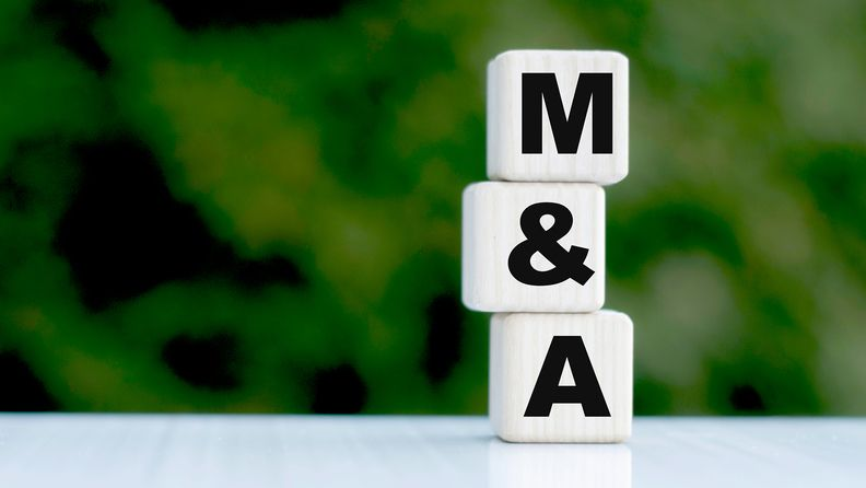 Concept of the phrase M&A on cubes on a green background