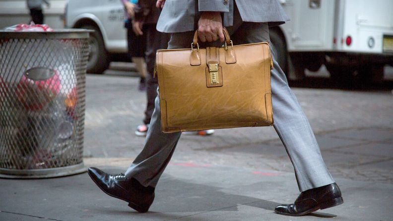 A man with a brief case walks down Wall Street in lower Manhattan near the New York Stock Exchange