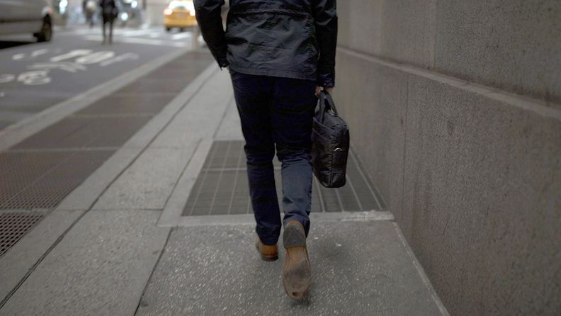 man walking with briefcase on city sidewalk
