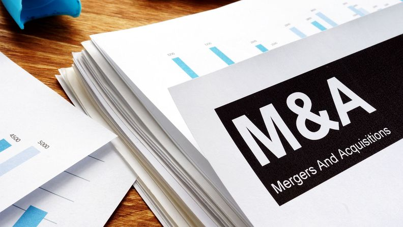 Documents about mergers and acquisitions (M&A) with a pen