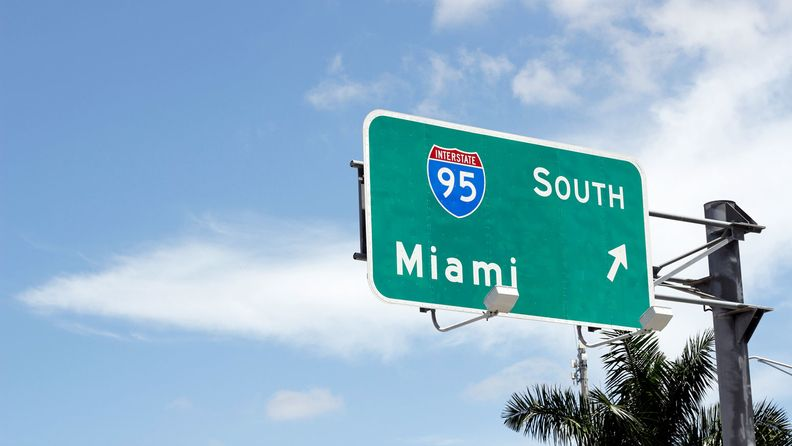 Large road sign signaling the way to go south to Miami on Interstate 95 in Florida.