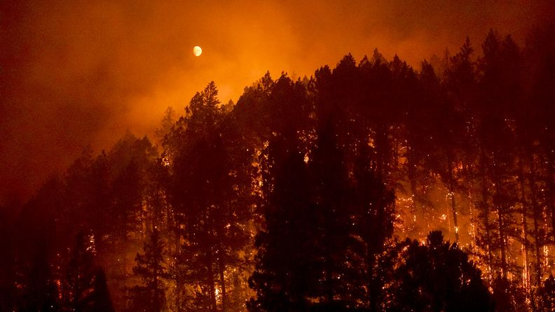 The moon glows red as a hillside burns during the Glass Fire in Napa County, Calif., on Sept. 27, 2020.