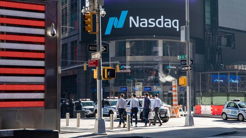 Pedestrians pass in front of the Nasdaq MarketSite in New York, on Nov. 9, 2020