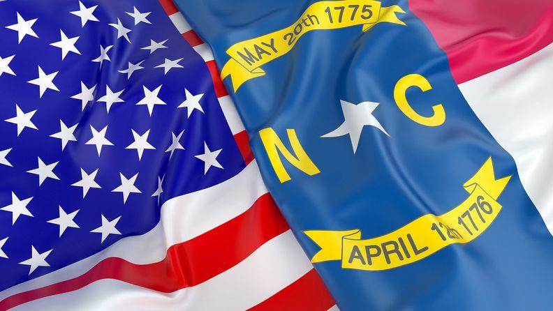 Close-up of USA flag with flag of North Carolina