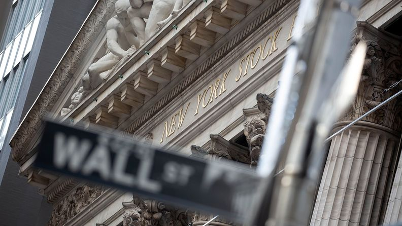 Wall Street street sign out of focus in front of the New York Stock Exchange