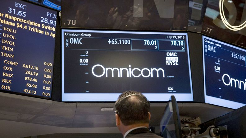 A trader works in front of a monitor displaying the Omnicom Group Inc. logo on the floor of the New York Stock Exchange.