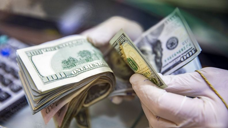A worker wearing protective gloves counts U.S. dollar banknotes at a currency exchange